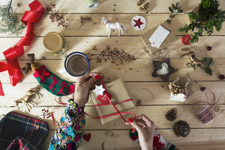 doityourself: woman decorating a Christmas present with a branch of holly, Do-it-yourself Christmas decoration