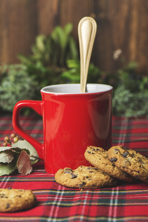 chocolate chips: Red cup of coffee, vanilla cookies with chocolate chips on checkered tablecloth