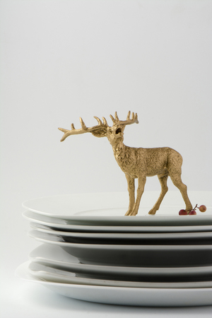 Plates stacked dishes and clean white  and gold reindeer tableware, conceptual food