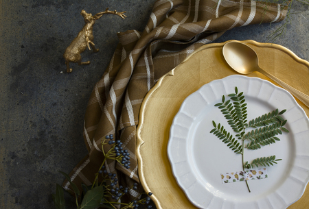 place setting: Holiday Gold place setting, napkin brown plaid, on grunge background