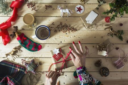 Woman decorating a christmas present with a branch of holly stock 48133593 woman decorating a christmas present with a branch of holly do it yourself christmas decoration solutioingenieria Images