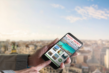 travel guide: phone in the hand of a woman, with the website of travel agencies and city skyline background.