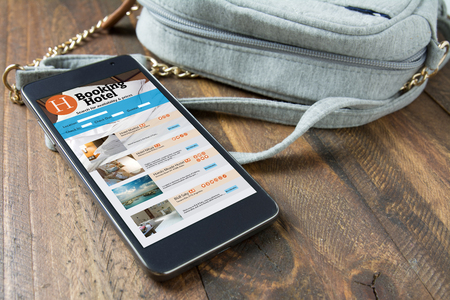 hotel booking: smart phone, with online hotel booking next to the womans purse. Travel and tourism concept