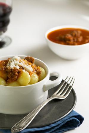 tomato puree: traditional homemade potato gnocchi with tomato puree and grated parmesan in white bowl