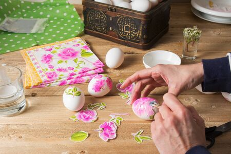 Apply woman PVA glue on colored Easter egg, with the technique of decoupage