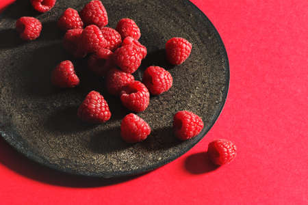 luscious: Fresh raspberries on rustic black plate, red background. From above Stock Photo