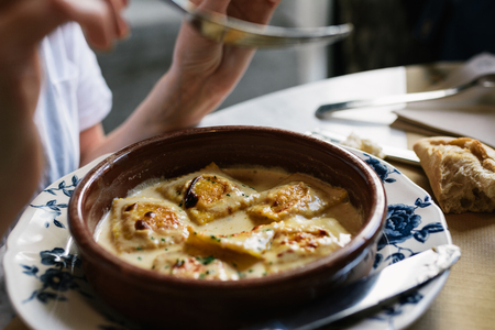 tortellini: Person eating ravioli with gratin cheese, on the antique plate in restaurant Stock Photo