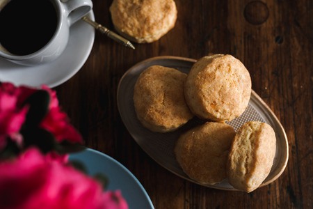 English cheese scones, on rustic wood next to the coffee cup