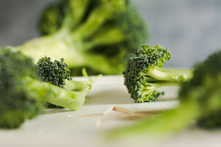 Small pieces of raw broccoli on white wood, Selective focus