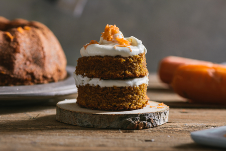 Mini carrot cake, stuffed with cream cheese, on rustic wood plate, close up