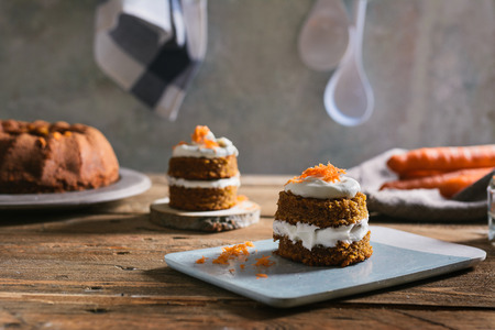 Mini carrot cake, stuffed with cream cheese, on blue concrete dish, on rustic wood