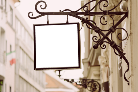 Blank square signboard, hanging from wrought iron bracket, in the city, classic architecture buildings background. Stock Photo
