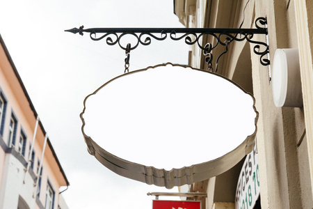 Blank Oval Signage hanging from wrought iron bracket, in the city