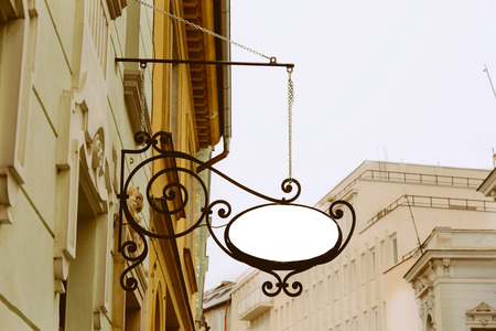 Blank Oval signboard, hanging from wrought iron bracket, in the city, classic architecture buildings background.