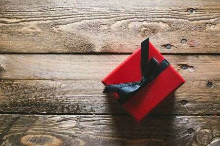 Red Gift box, on wooden table with black ribbon, from above