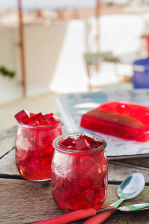 red jelly, cut into dice, inside two glasses of glass, on the table. outdoor