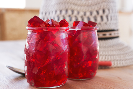red jelly, cut into dice, inside two glasses of glass, on the table Stok Fotoğraf
