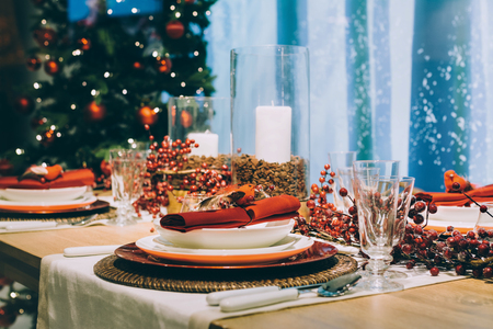 Festive place setting table, next to the Christmas tree
