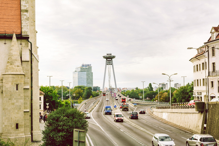 BRATISLAVA, SLOVAKIA: OCTOBER 03, 2016: Traffic and most of the SNP (New Bridge) of the Slovak National Uprising, crossing the Danube River in Bratislava, on the left the Cathedral of St. Martin, Slovakia Sajtókép