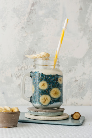 Chia smoothie, with fresh platanos and coconut and blueberries milk. on stone plate Banco de Imagens