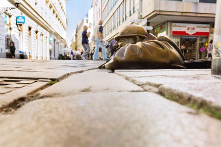 BRATISLAVA, SLOVAKIA: SEPTEMBER 30, 2016:  Historic center. Cumil statue, man peeking out from under a manhole cover . Popular attraction by artist Victor Hulik, 1997.