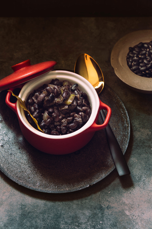 Stew of black beans and vegetables, in red ceramic casserole Stock Photo