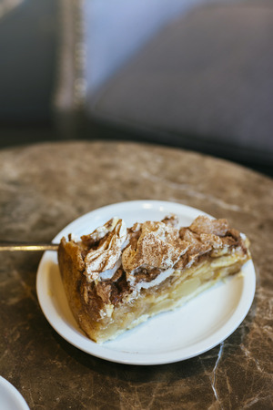 apple pie and swiss meringue, on brown marble table in the cafeteria