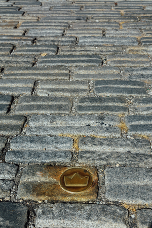 Slovakia, Bratislava. Brass crown marker in cobblestone streets show location of the coronation walk. Old town