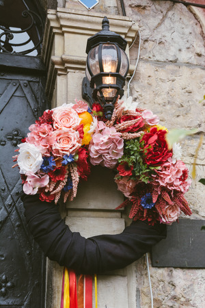 Christmas wreath decorated with colorful flowers, hanging in the entrance of the old Central European style house