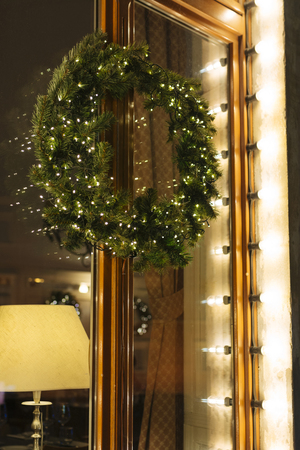 Christmas pine wreath decorated with lights, hanging in the entrance of the home Stock Photo