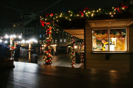 European Christmas market, stall with pine branches and garland of lights, in Warsaw Old Town Market Square, at night