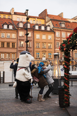 European Christmas Market: tourists making a selfie next to a bear, in Warsaw Old Town Market Square,