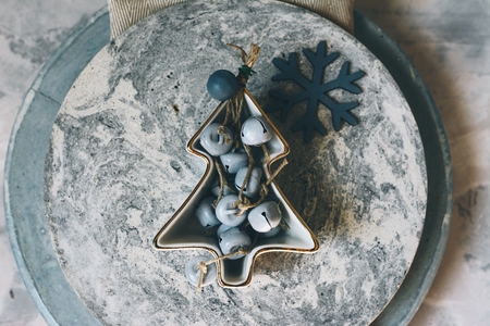 Christmas table set, concrete plates made by hand decorated with bowl and jinglebells, on light blue rustic background.