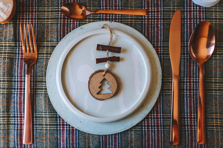 Holiday copper place setting, funny Christmas table dishes decorated with wooden ornaments and natural pine branches, on well plaid tablecloth, from above