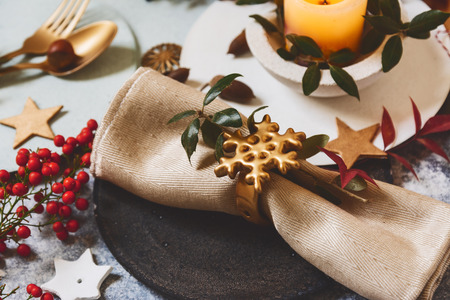 Holiday table setting, black plate with golden napkin holder with star shape, on rustic texture, surrounded by ornaments nandine branches and burning candles Stock Photo