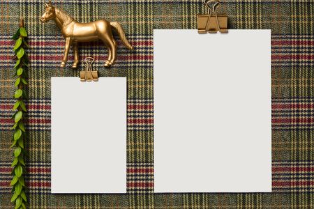 Empty holiday menu, decorated with golden ornaments, on the table with checkered tablecloth, From above. Christmas background or thanksgiving