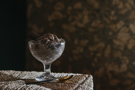 Chocolate mousse in glass cup, on wicker table. mystic light food