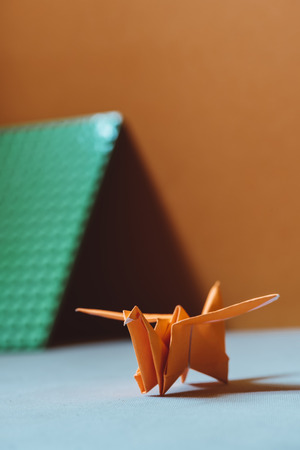 Orange origami bird, a bird made of paper-origami. (Soft focus), on light colored fabric cushion