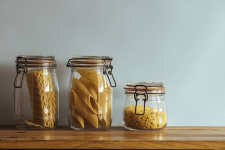Glass jars with raw pasta, on the kitchen shelf, in front of the blue wall