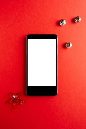 Christmas empty mobile phone on red background, Holiday planning and jingle bells decoration.