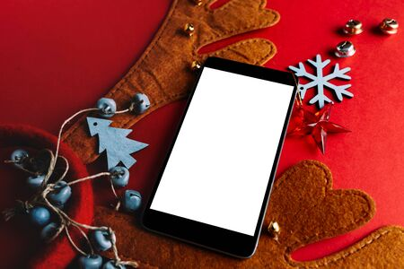 Smartphone and reindeer antlers headband, red christmas background decorated with ornaments