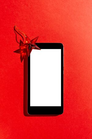 Mobile phone with blank screen and decorative star on red  background. Top view with copy space 版權商用圖片