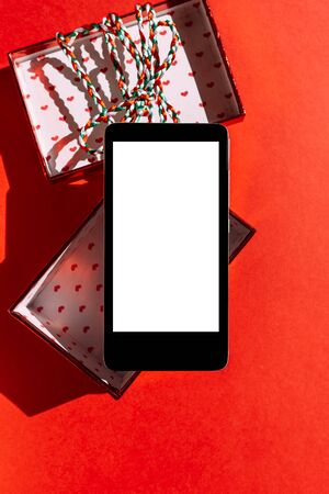 Christmas gift box with a smartphone inside, .A great gift for Christmas on red background. Modern technologies