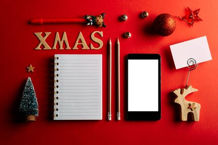 Christmas shopping list and mobile phone, Holiday planning red background, notebook and christmas decoration 版權商用圖片