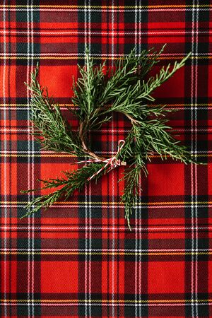 Christmas wreath of fresh pine branches on red checkered fabric, and copy space. Christmas conceptual background.