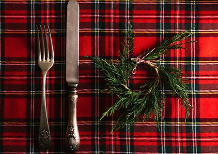 Vintage cutlery with small pine wreath on red checkered cloth, festive Menu. Christmas or thanksgiving background