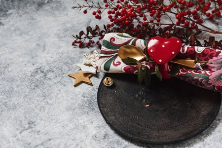 Holiday table setting, black plate with red heart-shaped napkin holder, on rustic texture