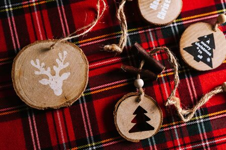 Modern wooden ornaments with a Christmas message for decoration, on a red tartan background. Christmas background