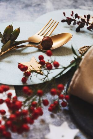 christmas table setting, golden cutlery and nandinas, on grunge table. Holiday dinner