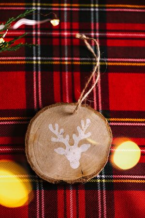 Round wooden ornament with the drawing of a reindeer, on the red checkered tablecloth and defocused lights, Christmas background. 版權商用圖片